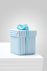 blue striped pattern gift box on white table.