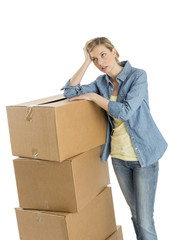Woman Looking Away While Leaning On Stacked Cardboard Boxes