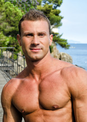 Handsome young muscle man smiling, outdoors