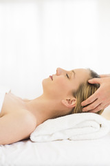Relaxed Woman Receiving Head Massage At Health Spa