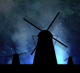 Silhouettes of windmills on night sky