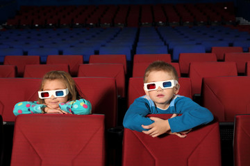 Two small children in 3D glasses watching a movie