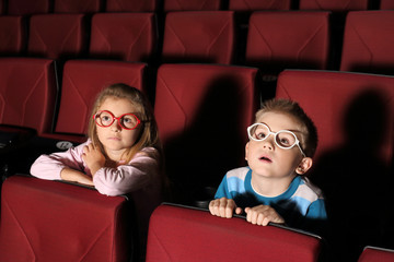 Little boy and girl watching a movie with interest