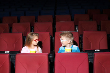 Little boy and girl in colored glasses with popcorn