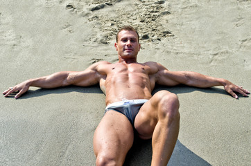 Young muscular man smiling, laying down on the beach