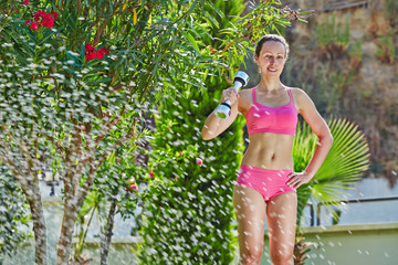Young woman does dumbbell exercises in morning garden