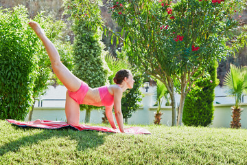 Young woman does leg swing on matting in morning garden