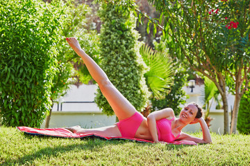 Young woman does leg swing lying on matting in morning garden
