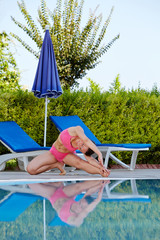 Young woman does exercises for flexibility on poolside