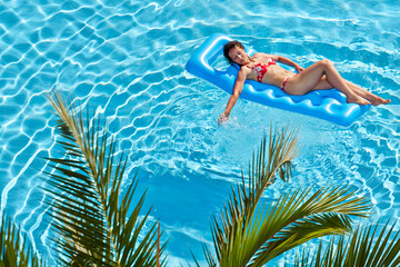 Woman in red swimsuit sunbathes on inflatable mattress in pool