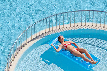 Young woman in swimsuit sunbathes lying on inflatable mattres