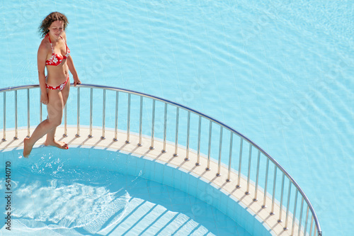 Young woman in red swimsuit walks on ledge separating two pools