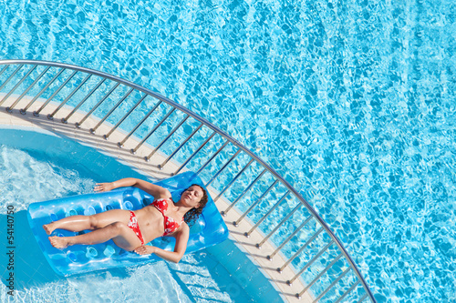 woman in red swimsuit bakes lying on inflatable mattress