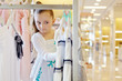 Little girl looks over dresses hanging on stand