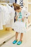 Little girl tries on short white skirt in clothing store