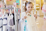 Little girl stands holding hanger with white gown in store