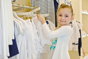 Little girl takes hanger with skirt from stand in clothing store