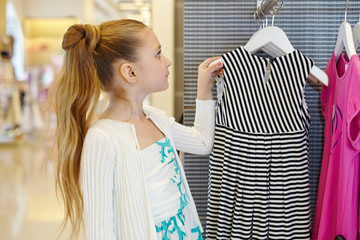 Little girl takes hanger with striped gown from stand