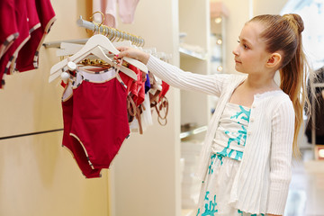 Little girl looks over closed swimsuit in clothing store