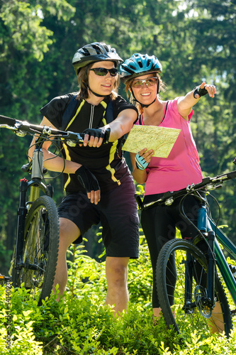 Cheerful bikers checking the map