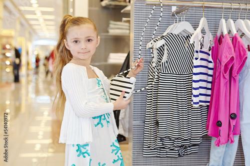 Little girl stands holding stylish striped female handbag