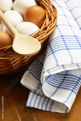 basket with chicken eggs, wooden spoon and dishcloth