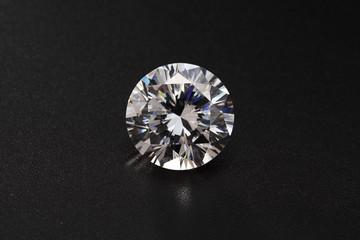 cut diamonds on shiny black surface close up.