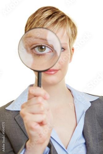 Junge Frau schaut durch eine Lupe