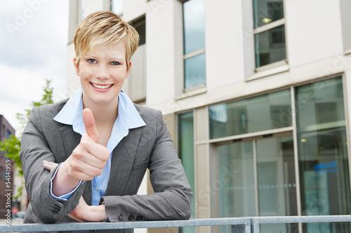 Junge Geschäftsfrau hält Daumen hoch