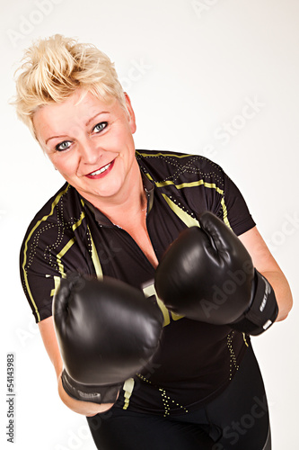 middelaged fitness woman boxing wearing boxing gloves and having
