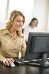 Happy Businesswoman Using Computer At Desk In Office