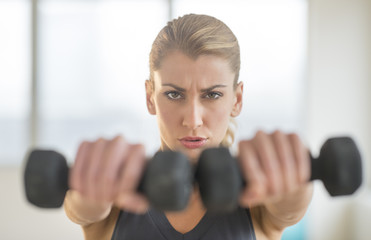 Dedicated Woman Lifting Dumbbells At Health Club