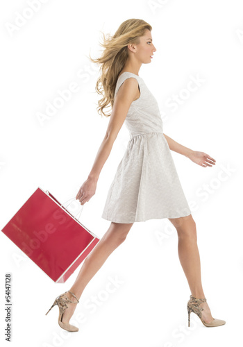 Side View Of Woman Walking With Shopping Bag