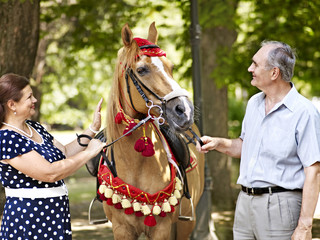 Happy old couple horseback riding outdoor.