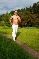 Man in white pants runs on the road