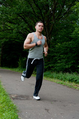 Man in black pants runs on the road