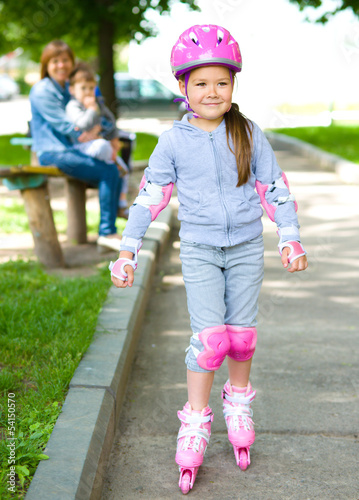 Happy little girl is skating on rollers
