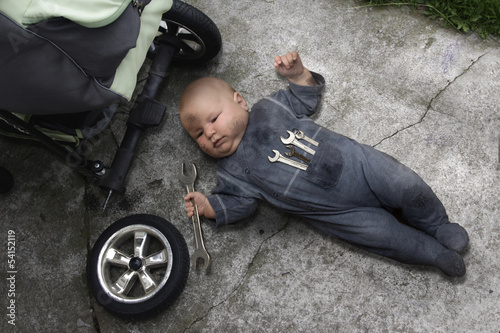 baby lying on the ground and repairing your stroller - 54152119