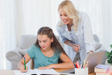 Mother helping her daughter during her homework