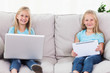 Twins using a laptop and a tablet sitting on a couch