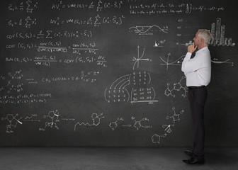 Elegant businessman looking at maths equations