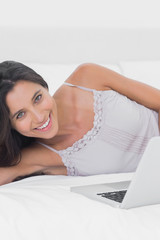 Woman using her laptop lying in bed