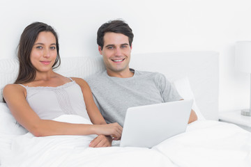 Portrait of a cheerful couple using a laptop