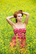 Young beautiful woman in the yellow rape field