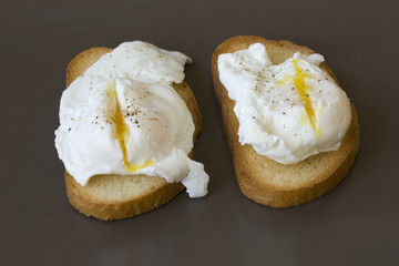 Classic breakfast - poached eggs on toast on a brown plate
