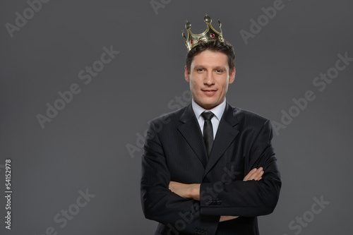 Business king. Confident businessman in crown standing isolated