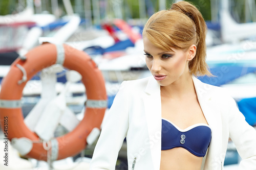 sexy fashionable woman standing in a port fashion style, yachts