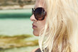 Beautiful blond woman in sunglasses on beach