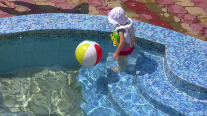 The little girl plays with a ball in water pool