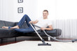 Young attractive man is cleaning vacuum on carpet.
